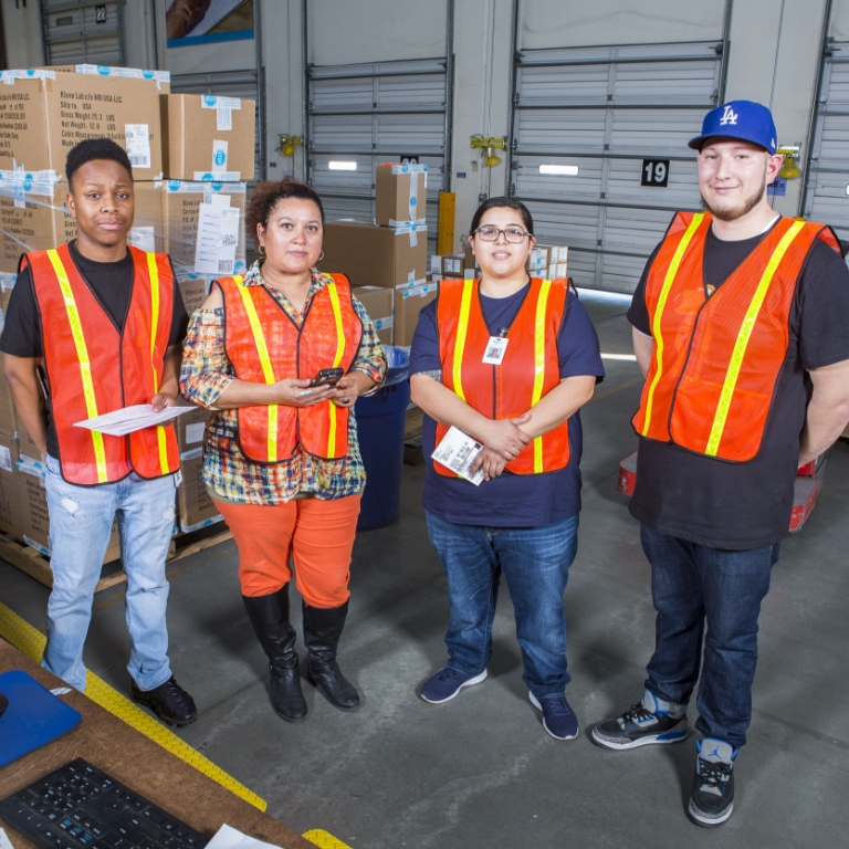 Four warehouse workers in orange hi-vis vests