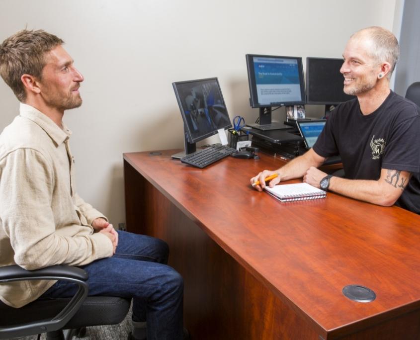 Man in beige shirt speaks with man in black shirt in office