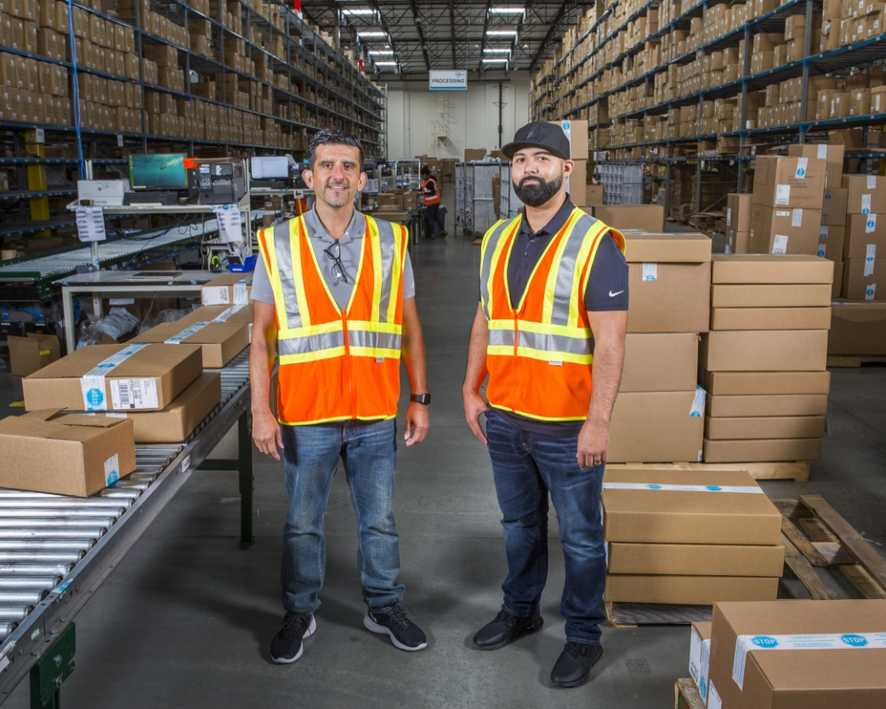 Two warehouse employees in orange hi-vis vests