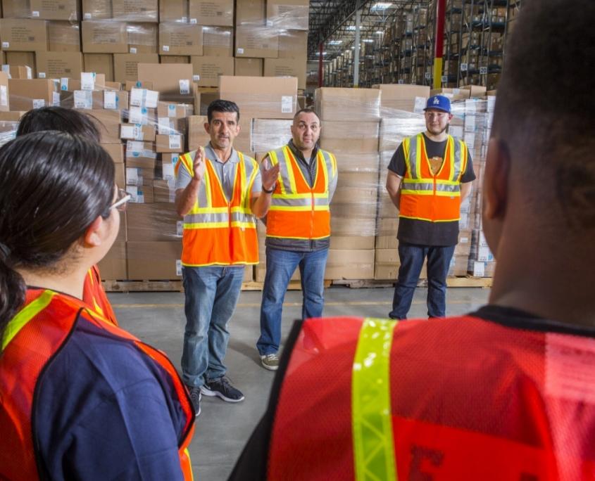 Warehouse manager with orange hi-vis vest leading team