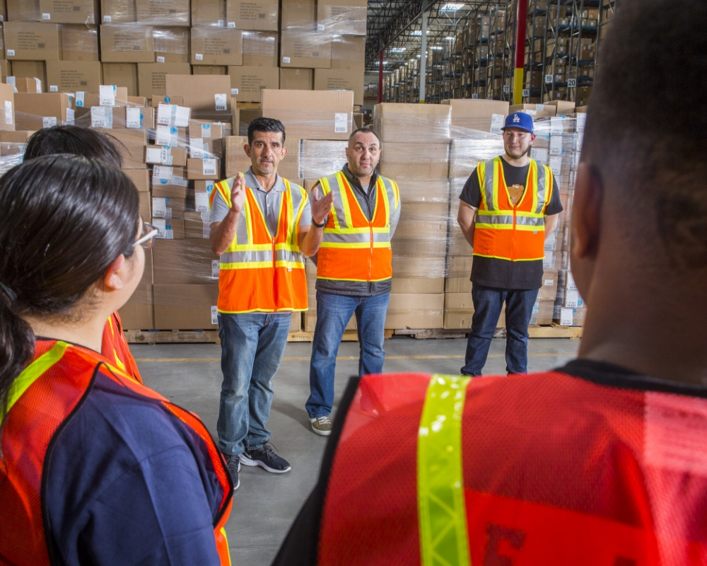 Warehouse manager with orange hi-vis vest leading team