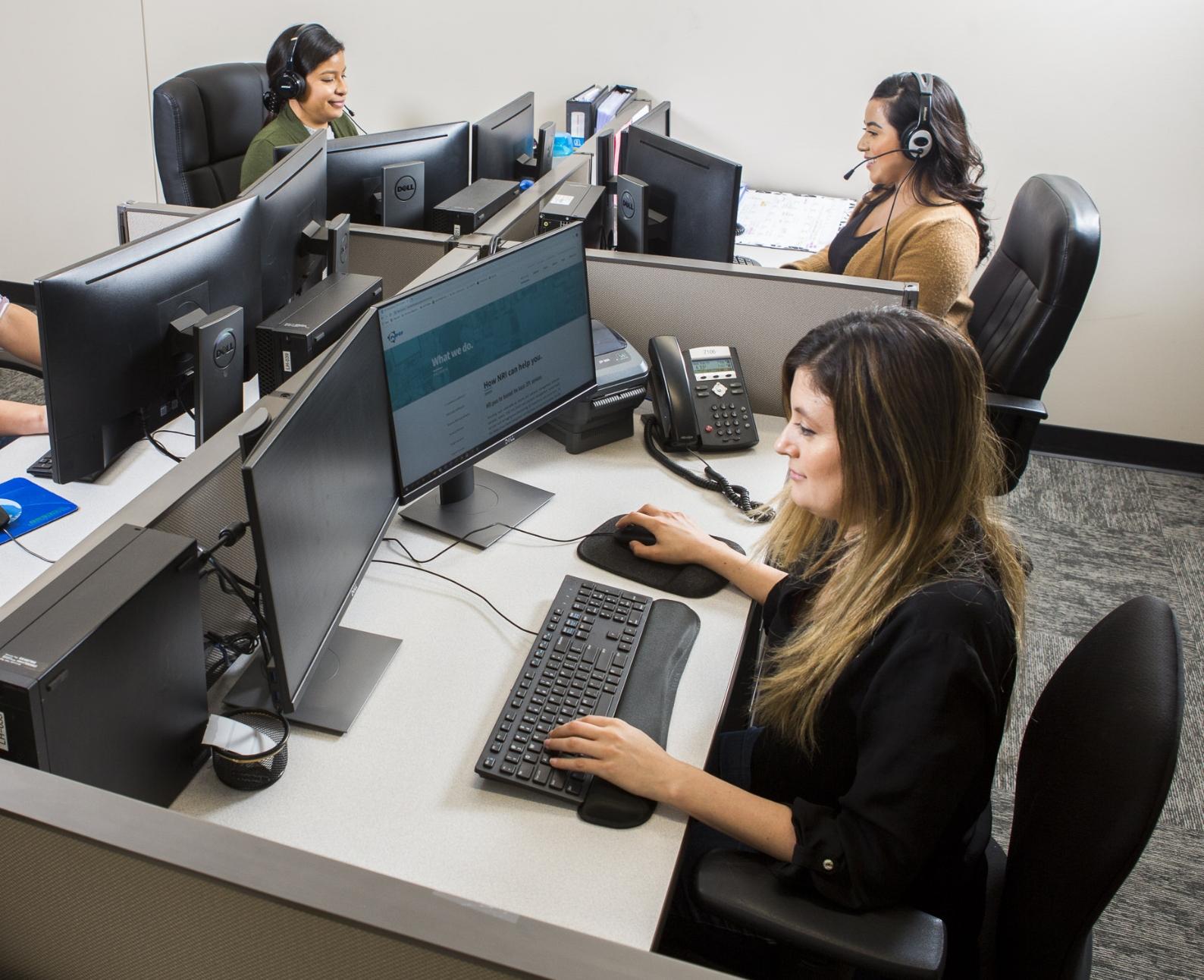 Three women wearing headsets working at desks