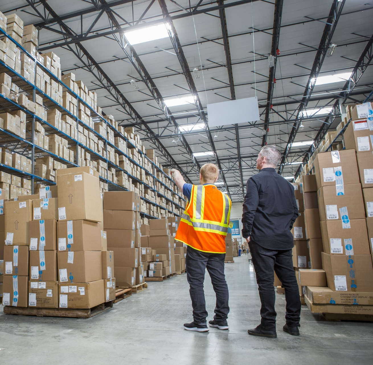Man in hi-vis vest pointing to boxes while man in black shirt looks in warehouse